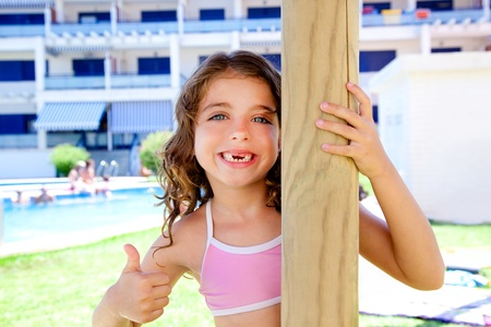 indented kid girl ok gesture in pool garden holding sunroof pole photo