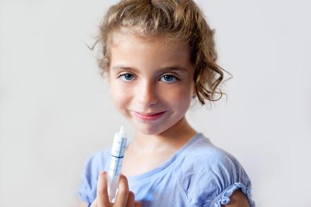 almost happy children kid girl with syringe of antibiotic medicine photo