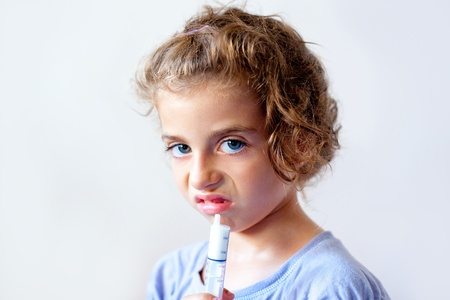 disgusting: Unhappy kid girl with syringe medicine dose funny expression Stock Photo