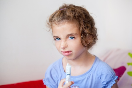 revulsion: Unhappy kid girl with syringe medicine dose funny expression Stock Photo