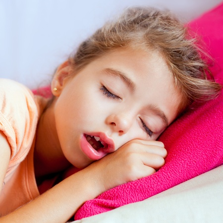 Deep sleeping children girl closeup portrait on pink pillow photo