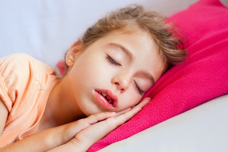 mouth closed: Deep sleeping children girl closeup portrait on pink pillow