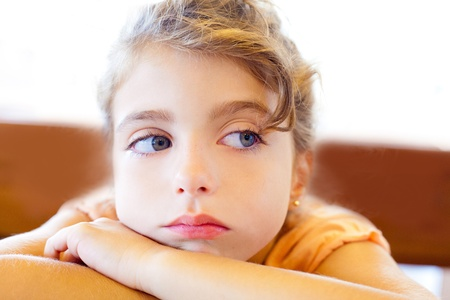 Blue eyes sad children girl crossed arms on table photo