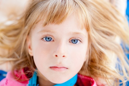Beautiful blond blue eyes girl lying closeup face photo