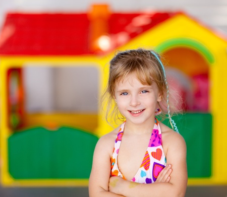 blond kid girl crossed arms in toy house playground photo