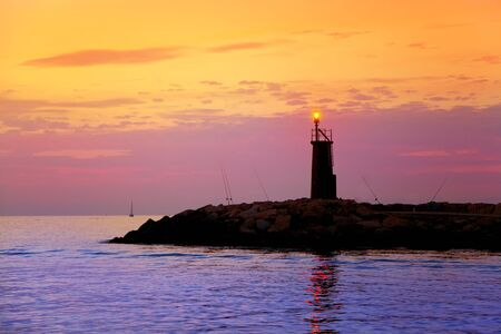 Sunrise lighthouse glowing in blue purple sea and orange sky Stock Photo - 10839384