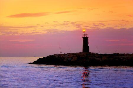 Sunrise lighthouse glowing in blue purple sea and orange sky Stock Photo - 10839384