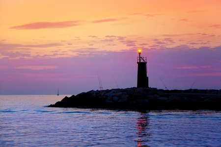 Sunrise lighthouse glowing in blue purple sea and orange sky Stock Photo - 10839382