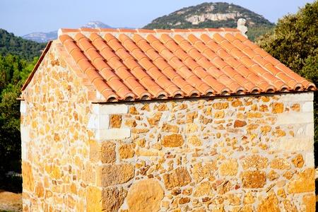 masonry stone little house in mediterranean forest photo
