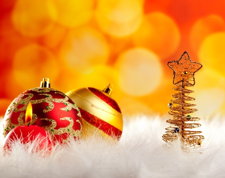 modern christmas baubles: christmas wire tree with candle and baubles in blurred lights background Stock Photo