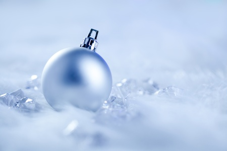christmas silver bauble on fur snow and ice cold winter photo