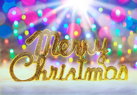 written text: Merry christmas written in gold with colorful glowing lights