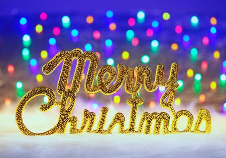 Merry christmas written in gold with colorful glowing lights photo