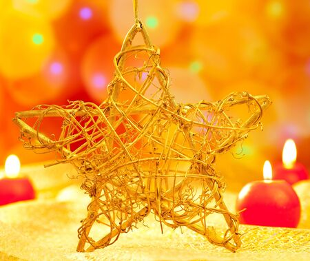Christmas golden branch star with candles in blurred lights photo