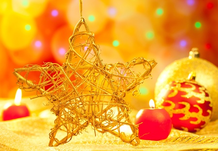 Christmas golden branch star with candles and baubles in blurred lights