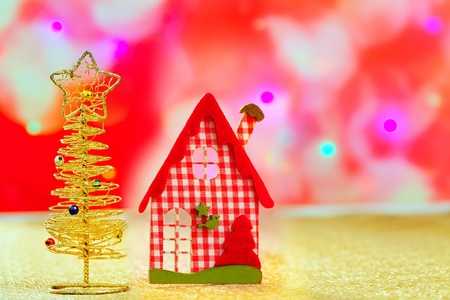Christmas golden tree and red vichy house in blurred lights photo