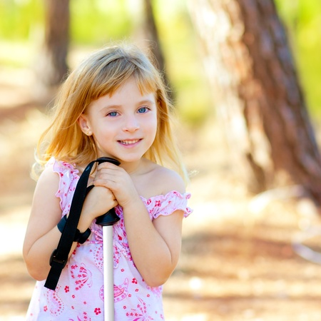 little girl smiling: Beautiful kid girl in park forest smiling with hiking pole Stock Photo