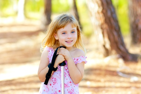 Beautiful kid girl in park forest smiling with trekking pole photo