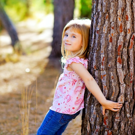 blond kid girl on autumn tree trunk in forest park photo