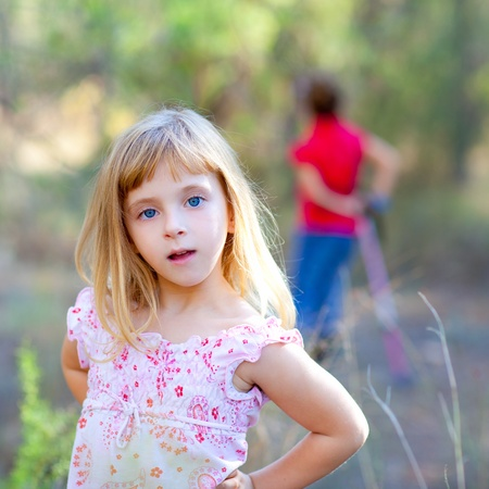 blond kid girl in forest park posing to camera photo