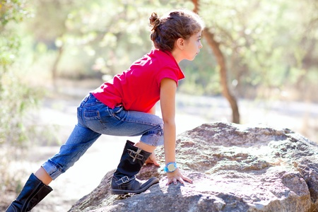 red jeans: Hiking little girl climbing a rock in forest outdoor Stock Photo