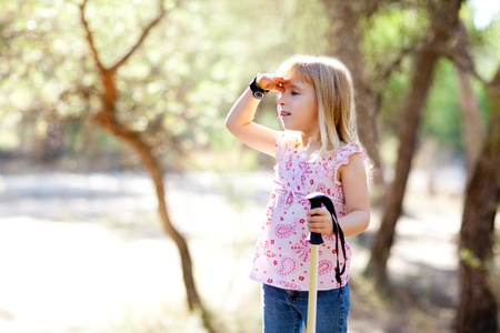 hiking kid girl searching hand in head in forest outdoor