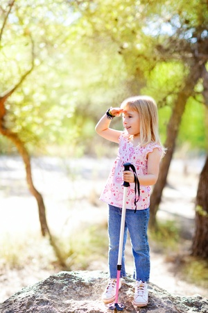 hiking kid girl searching hand in head in forest outdoor photo