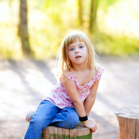 blond kid girl in tree trunk forest outdoor photo