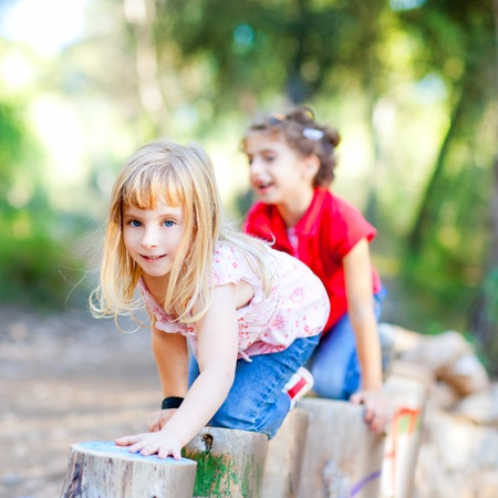 american children: kid girls playing on trunks knee walking in forest nature