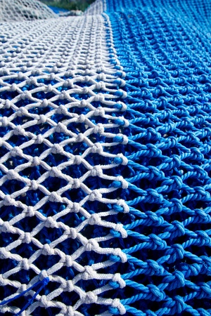 fish net: blue and white fishing nets with rope knots for trawling boats Stock Photo