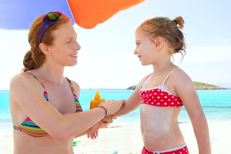 daughter and mother in beach with sunscreen in bikini photo