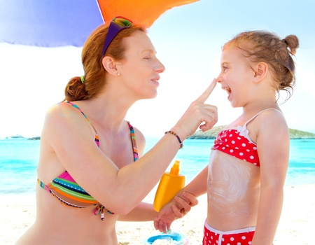 daughter and mother in beach with sunscreen in bikini Stock Photo - 11057900
