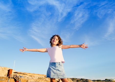 Girl open arms outdoor under blue sky with happy gesture Stock Photo