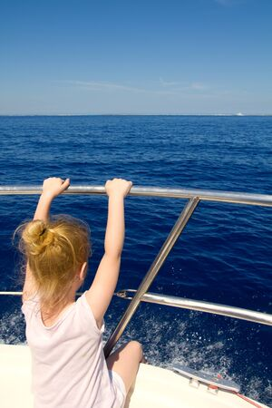 Blond little girl rear view sailing in boat in blue Ibiza sea photo