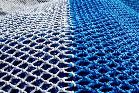 blue and white fishing nets with rope knots for trawling boats photo