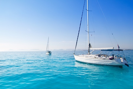 anchored sailboats in turquoise Formentera Illetes beach near Ibiza photo