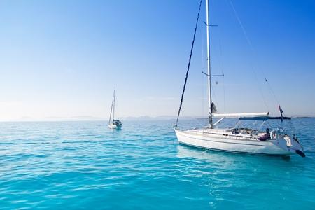 anchored sailboats in turquoise Formentera Illetes beach near Ibiza