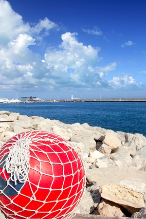 fishing nets: fishing red buoy with net in formentera port breakwater of Mediterranean sea Stock Photo