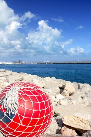 redes de pesca: pesca con red de boyas de color rojo en Formentera espigón del puerto del mar Mediterráneo