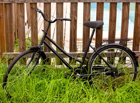parked bicycles: black grunge bicycle aged on a wood fence and grass Stock Photo
