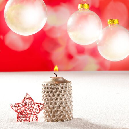 christmas silver candle and red star on snow and red with glass baubles photo