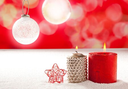 christmas silver red candles and star on snow with glass baubles photo