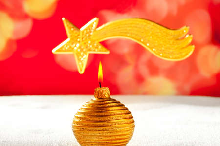 Christmas golden candle and bethlehem comet star on snow and red photo