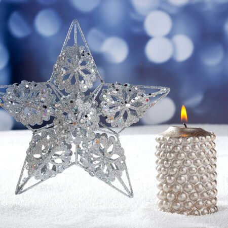 Christmas card of silver star and candle on snow and blue background photo