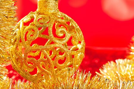 Christmas card golden bauble arabesque and tinsel on red background photo