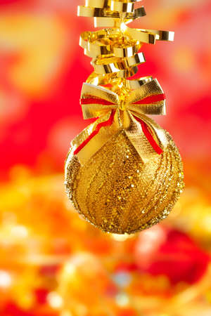 Christmas card tinsel golden glitter bauble ribbon loop on red blur background photo