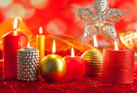 Christmas card candles red and golden in a row on blurred background photo