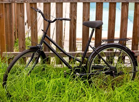 black grunge bicycle aged on a wood fence and grass photo