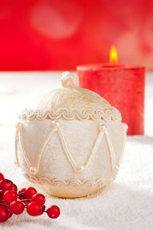 Christmas card of white velvet bauble and red candle on snow background photo