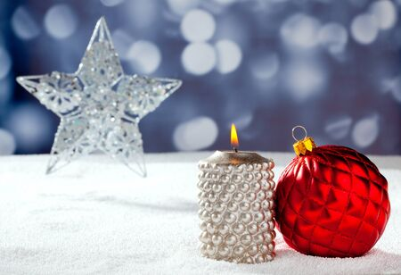 Christmas card of silver star bauble and candle on snow and blue background photo